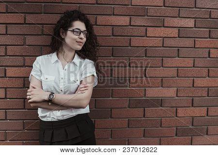 Young Confident American Woman With Black  Curly Hair Standing On Th Red Brick Wall Background And L