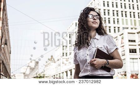 Confident And Pretty Young Woman With Black  Curly Hair Standing On The Buildings Background And Loo