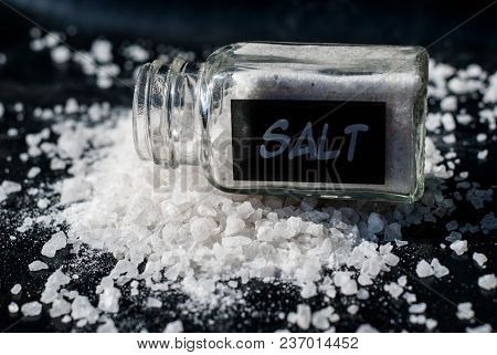 Salt Shaker With Sea Salt On A Black Background.