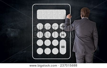 Businessman Paints Calculator Icon On Blackboard Concept.