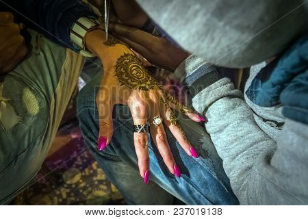 Artist Drawing Henna Pattern On Woman Hand, A Tradition Art Of Indian Bride, Mehndi Also Become Fash