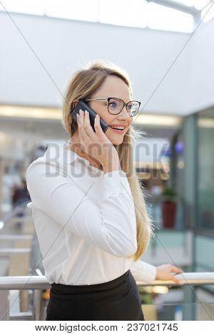 Young Blonde Caucasian Businesswoman Calling In Business Center