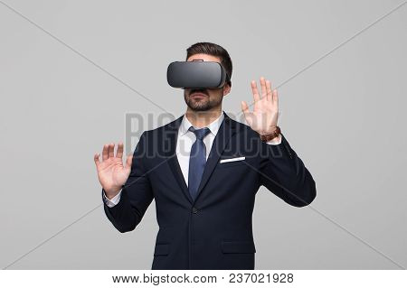 Young Professional Businessman In Vr Headset Touching Imaginary Interface