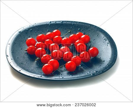 Red Cherry Tomatoes On Twigs With Water Drops On Black Plate