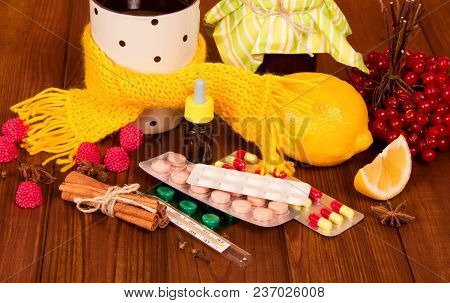 Hot Herbal Tea With Lemon And Spices, Thermometer, Pills And Nasal Drops For Treatment On Brown Wood