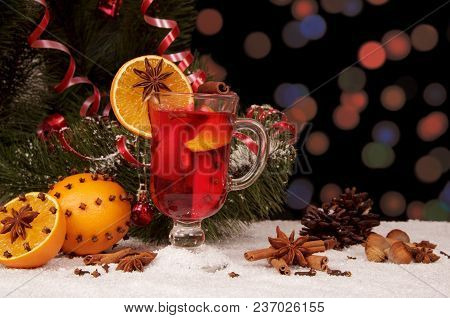 Hot Winter Drink, Fruits, Nuts, Cones And Serpentine On Background Of Artificial Snow