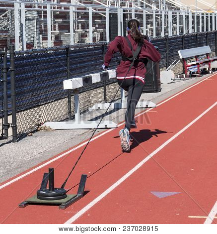 A High School Girl Pulls A Sled With 20 Pounds On It Down A Track Next To The Bleachers In The Cold.