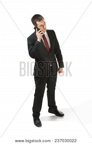 Three-quarter Portrait Of Businessman With Serious Face. Confident Professional With Mobile Phone. D
