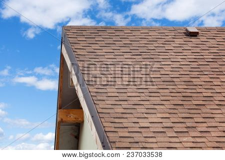 Roof Under Construction With New Asphalt Tile Roof And Rain Gutter