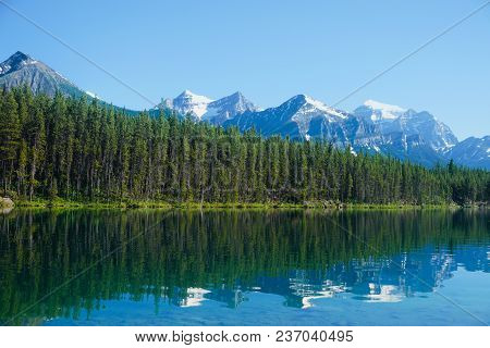 Mountains And Trees Reflected In A Mountain Lake