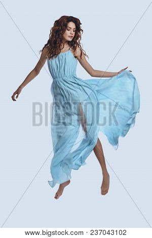 Levitation. Full Length Studio Shot Of Attractive Young Woman In Elegant Dress Hovering Against Grey