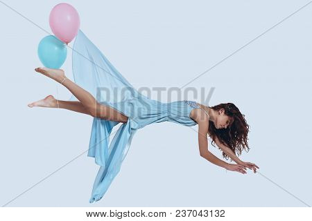 Flying Beauty. Studio Shot Of Attractive Young Woman In Elegant Dress Keeping Arms Outstretched Whil