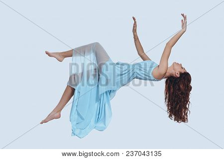 Flying So High. Studio Shot Of Attractive Young Woman In Elegant Dress Keeping Arms Outstretched Whi