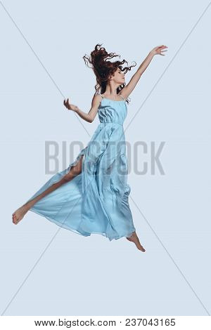 Reaching The Sky. Full Length Studio Shot Of Attractive Young Woman In Elegant Dress Gesturing While