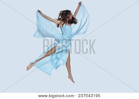 Flying. Full Length Studio Shot Of Attractive Young Woman In Elegant Dress Keeping Arms Outstretched