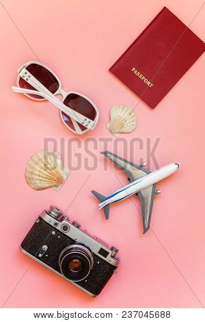 Flat Lay With Plane, Vintage Camera, Passport, Sunglasses And Shell On Pink Colourful Pastel Trendy