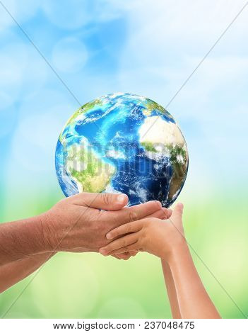 The Man Holding Planet Earth With Baby Over Nature Background. Ecology Concept, Earth Day, World Env