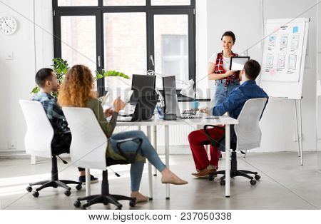 business, technology and people concept - woman showing tablet pc computer and user interface design on flip chart to creative team at office presentation
