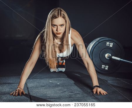 Athletic Sexy Blond Girl With A Perfect Figure In Shorts Doing Push Ups In Gym . White Beauty In Gym