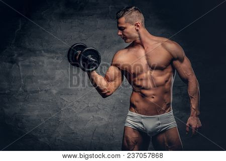 Portrait Of Shirtless Strong Suntanned Muscular Male Holds Dumbbell.