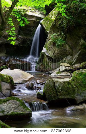 Small Waterfall Among The Rocks. Beautiful In Ancient Woods