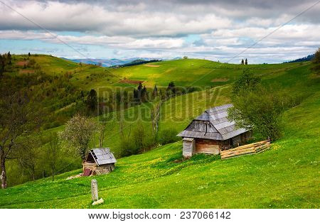 Woodshed On A Grassy Hillside On A Cloudy Day. Village Outskirts With Rural Fields In Mountainous Ar