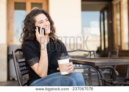 Cute Caucasian Girl Relaxing At The Cafe And Talking On The Phone
