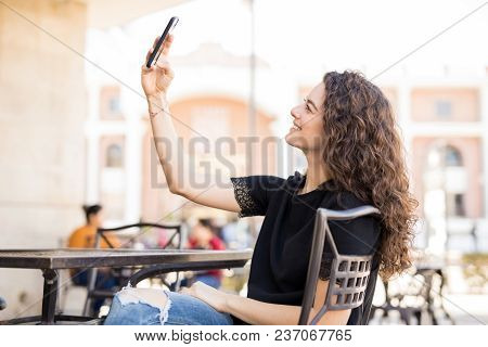 Gorgeous Young Brunette Taking A Selfie With Her Smartphone While Sitting At An Outdoor Cafe
