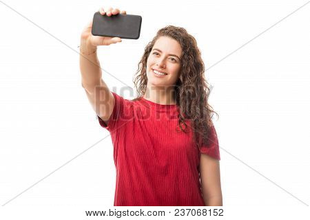 Gorgeous Young Woman Taking A Selfie With Her Smart Phone Against White Background