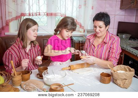 Mom Teaching Her Two Daughters Cooking On The Kitchen.