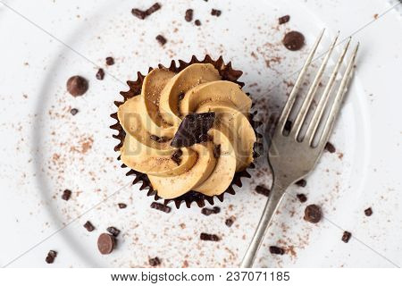 Salted Caramel Cupcake On White Plate With Fork, Dusted With Cocoa Powder And Chocolate Sprinkles, O