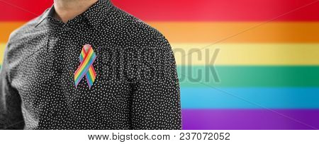 lgbt, same-sex relationships and homosexual concept - close up of man with gay pride awareness ribbon on his chest over rainbow background