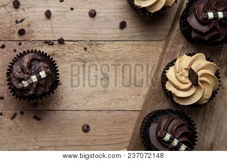 Overhead Chocolate Cupcakes On Wooden Table With Chocolate Chip Sprinkles