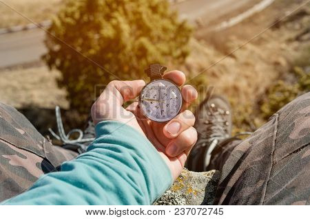 Hiker Sitting On A High Rock Holds A Compass In Front Of Her Feet In Trekking Boots And A High Cliff