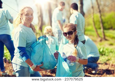 volunteering, charity, people and ecology concept - group of happy volunteers with garbage bags cleaning area in park