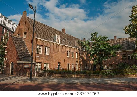 S-hertogenbosch, Southern Netherlands - July 01, 2017. Street With Big Brick House, Trees In A Garde