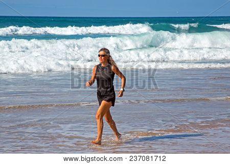 Sportive mature woman jogging along the beach at the atlantic ocean