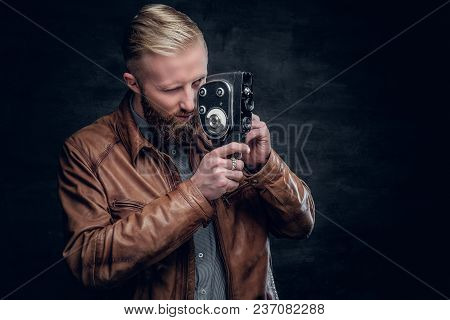 Portrait Of Blond Bearded Male Dressed In Brown Leather Jacket Holds Vintage 8mm Video Camera.