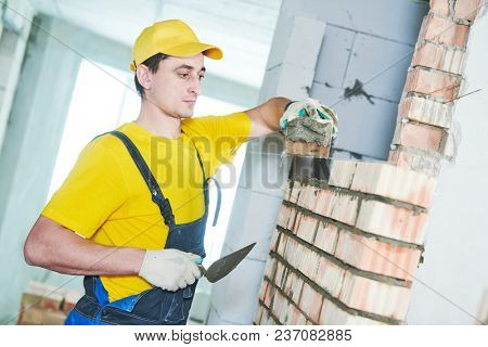 bricklaying. Construction worker laying bricks wall