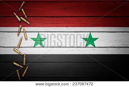 Syria flag with bullets on wooden background, Conceptual image for war, violence, conflicts