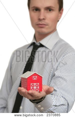 The Man Holds The Red House In A Hand