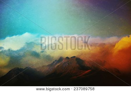 Atmospheric Grunge Textured Image Of Clouds Rolling In Over Mountain Peaks In Aoraki National Park.
