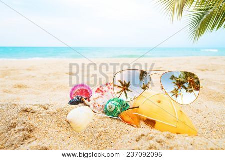 Sunglasses And Seashell On The Sandy Tropical Beach With Clear Blue Sky. Leisure In Summer And Summe