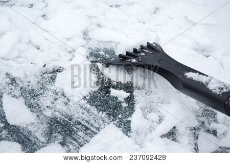 Removing Snow And Ice On The Car Windshield