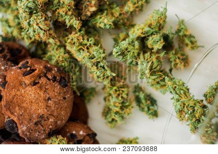 Cookies With Cannabis And Buds Of Marijuana Top View On The Table. Concept Of Cooking With Cannabis