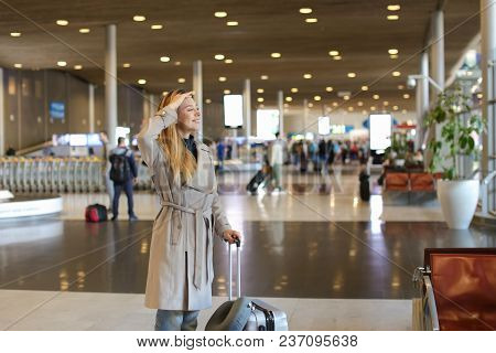 Young Female Person Walking In Airport Waiting Room With Valise And Neck Pillow. Concept Of Travelin