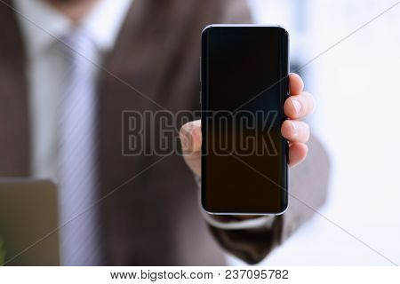 Male Arm In Suit Show In Camera Phone Display Screen Closeup. Read News Mania Send Sms Chat Addict U