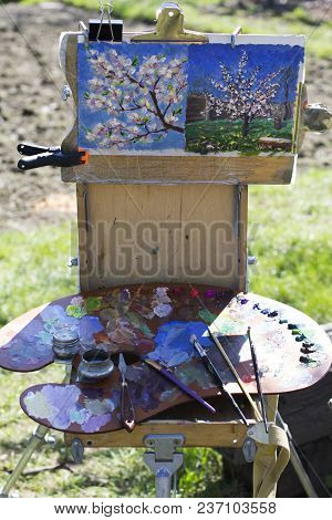 Plein Air Etude With Two Paintings And A Palette. A Palette With Multicolored Paints And Brushes Lie