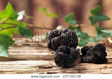 Black Truffles And Leaves On Old Wooden Table.