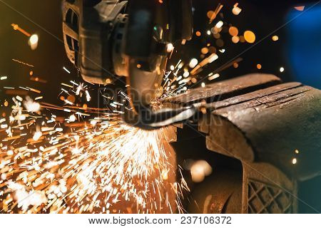 Working Metal Grinder Or Electric Angle Cutter With Sparkles In The Industrial Workshop